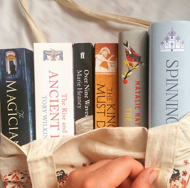 Tote bag with books coming out from the top - The Magicians by Lev Grossman, The Rise and Fall of Ancient Egypt by Toby Wilkinson, Over Nine Waves by Marie Heaney, The King Must Die by Mary Renault, The Children of Jocasta by Natalie Haynes, and Spinning Silver by Naomi Novik