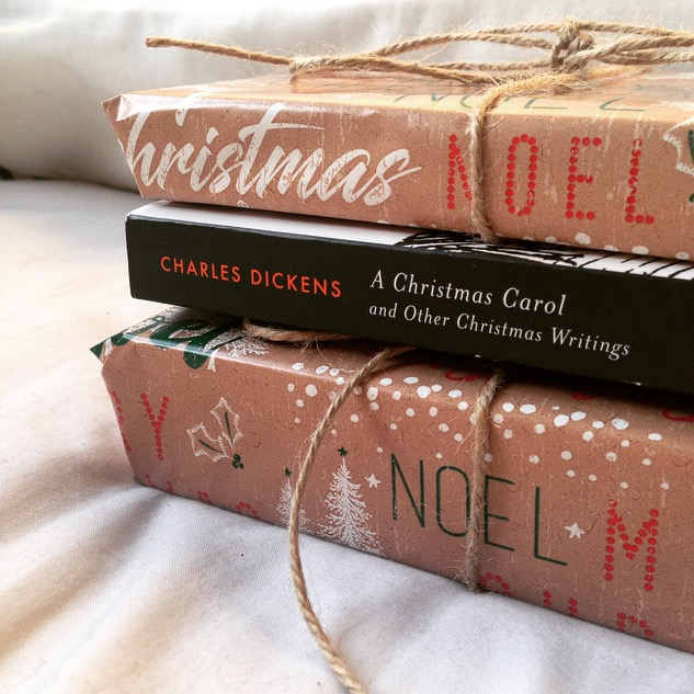 A Christmas Carol book between two book shaped christmas presents