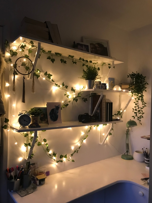 desk in my bedroom with 3 shelves above it decorated with ivy and fairy lights