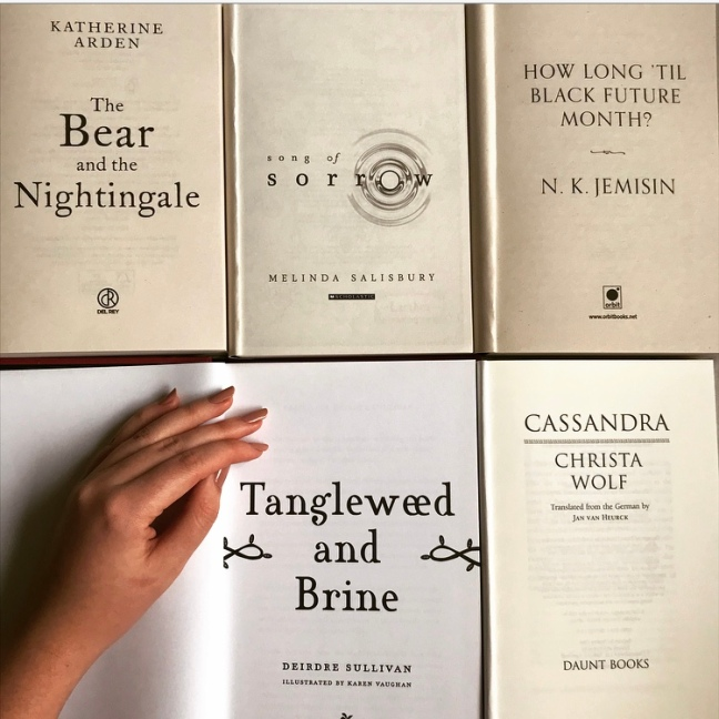 Open pages of books - female fantasy authors - includes The Bear and the Nightingale by Katherine Arden, Song of Sorrow by Melinda Salisbury, How Long Til Black Future Month by N.K. Jemisin, Tangleweed and Brine by Deirdre Sullivan, Cassandra by Christa Wolf