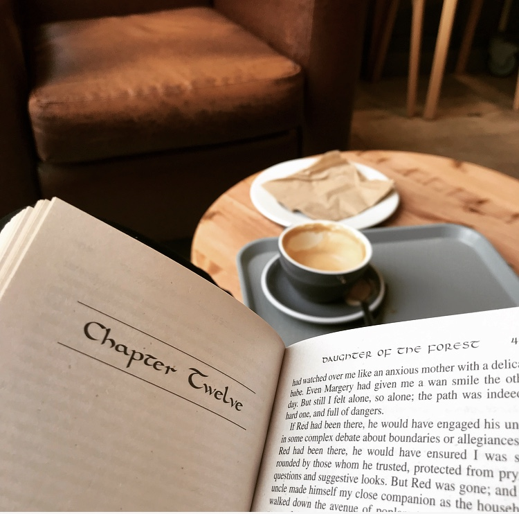 Open book with coffee in background, Waterstones cafe. Book is open on chapter twelve of Daughter of the Forest by Juliet Marillier, read for the book club Myth-Take Reads